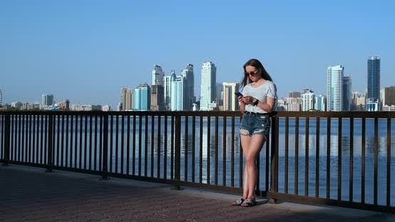 Thumbnail for Girl on the Background of the Big City and the Bay Holding a Smartphone in Sunglasses