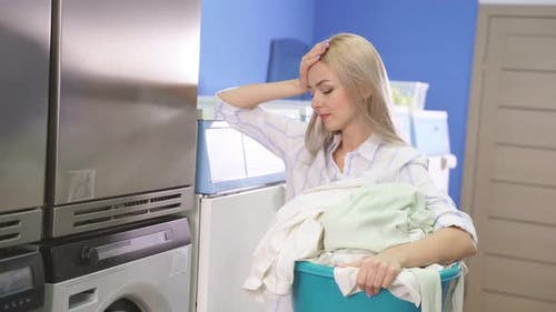 Woman in a Public Laundry Waiting for Laundry Laundry Room