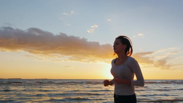 Thumbnail for Attractive Young Woman Is Running Along the Seashore at Sunset. Engage in Sports - Healthy Lifestyle