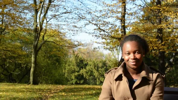 Thumbnail for Young Beautiful African Happy Girl Sits on Bench in Woods and Stares To Camera