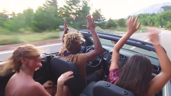 Thumbnail for Young friends enjoying their road trip in convertible car