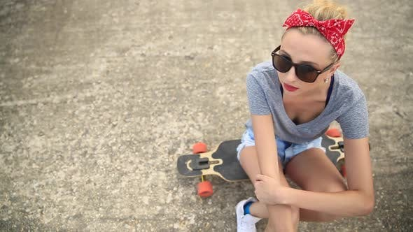 Portrait of a young woman with sunglasses, a red bandana and a longboard skateboard