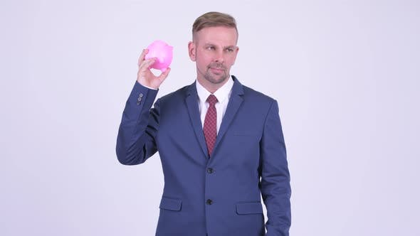 Thumbnail for Blonde Businessman Shaking Piggy Bank and Shrugging Shoulders