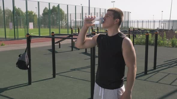 Sportsman Drinking Water At Outdoor Workout