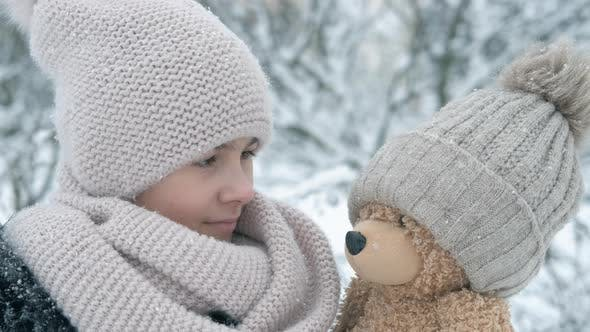 Play with teddy in winter.