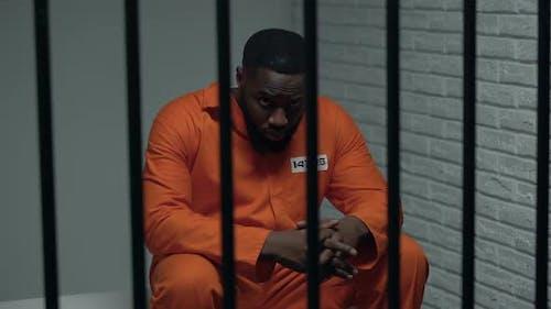 Nachdenklicher afroamerikanischer Gefangener wartet auf Besucher und verbüßt lebenslange Haftstrafe