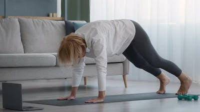 Senior Lady Doing Yoga Stretching Having Online Lesson At Home