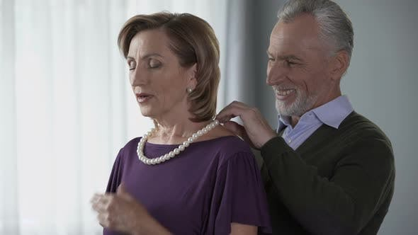 Thumbnail for Elderly Man Putting Pearl Necklace on Wife and Kissing Her, Celebration, Present