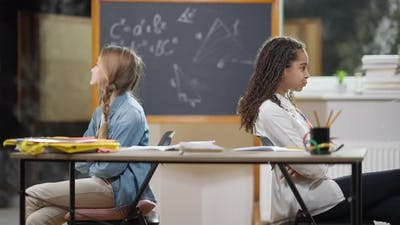 Argued Schoolgirls Sitting Back to Back in Classroom Talking and Showing Tongue Out
