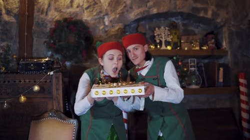 Joyful elves with magic book in decorated room at Christmas.