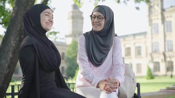 Thumbnail for Portrait of Confident Positive Woman in Hijab and Eyeglasses Sitting with Friend Outdoors and