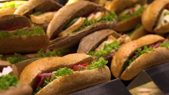 Thumbnail for Closeup on Sub Sandwiches on Display on a Counter in a Store