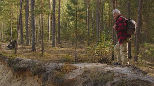 Middle-aged Man Is Walking on High Shore of River in Forest at Autumn Day, Ecotourism and Fishing at