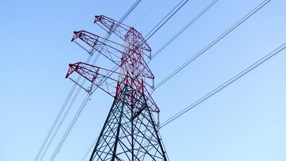 Stromübertragungsleitungen und Turm gegen blauen Himmel