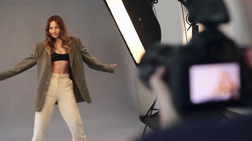 A Female Model Poses for a Male Photographer.