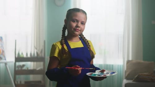 Portrait of Small Girl In Blue Apron