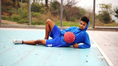 Young African American Laying on the Floor of the Playing Field and Playing with Basketball Ball