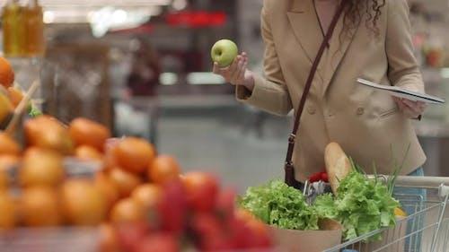 Woman Shopping According to Checklist