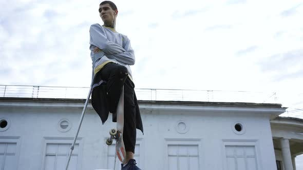 Thumbnail for Handsome Young Man with One Leg on Crutches Training with Skateboard
