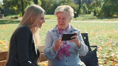 Elder Grandmother Showing Her Granddaughter Photos on Smartphone