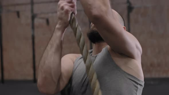 Sportsman Climbing a Tightrope in Gym