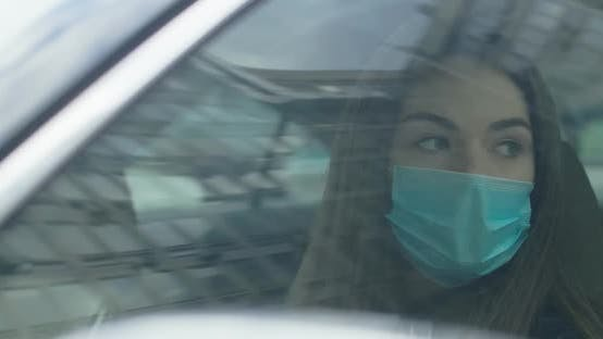 Thumbnail for Young Brunette Woman in Protective Mask Sneezing and Coughing As Sitting on Driver's Seat. Portrait