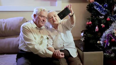 An elderly couple takes a selfie near the Christmas tree at home for Christmas