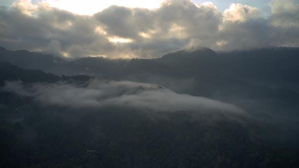 Thumbnail for Drohne über Morgenwolken über Wäldern und Bergen