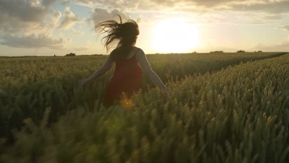 Beautiful Woman in a Red Dress Runs Against the Sunset