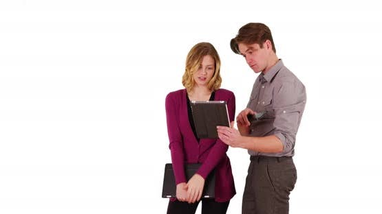 Businessman showing female coworker something on tablet in studio with copyspace