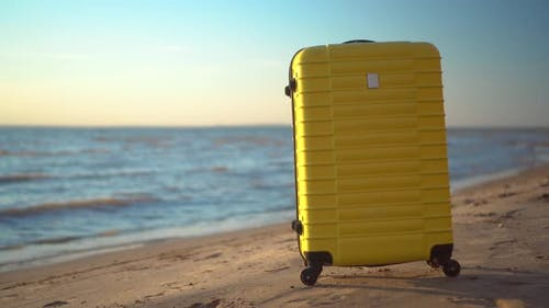 A Yellow Suitcase Stands on the Beach Against the Background of the Sea. Travel Suitcase.