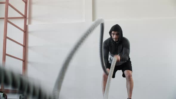 Handsome Muscular Man Training Rope Exercise During Intensive Workout in Gym