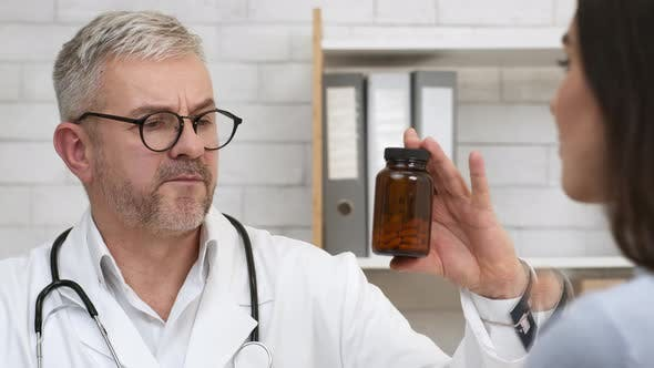 Male Doctor Prescribing Medication Showing Medicine Bottle To Patient Indoors