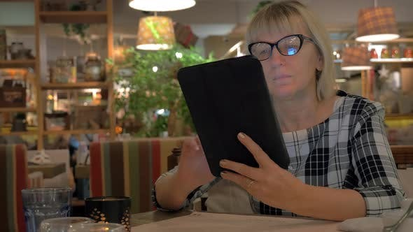 Cover Image for Senior Woman Browsing on Touch Pad in Cafe