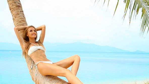 Thumbnail for Sexy Girl in Bikini Relaxing on Palm at the Beach