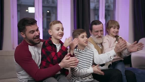 Thumbnail for Kids, their Father and Grandfather which Emotionally Watching Football Game