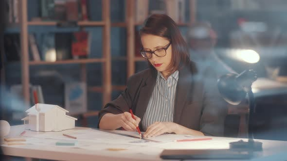 Thumbnail for Thoughtful Female Architect Working on Floor Plan at Desk in Office