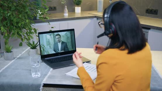 Woman in Headset Holding Video Conference with Male Colleague