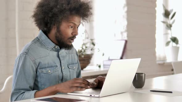 Shocked Creative African Man Wondering and Working on Laptop