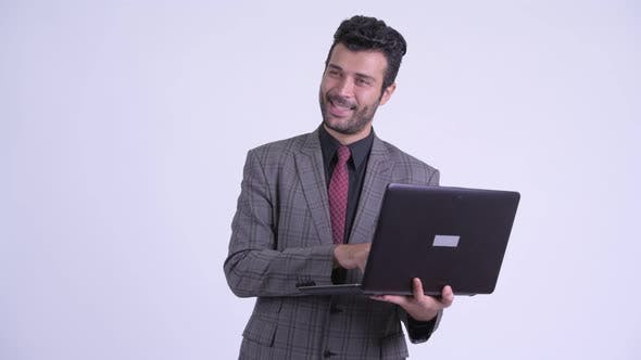 Thumbnail for Happy Bearded Persian Businessman Thinking While Using Laptop