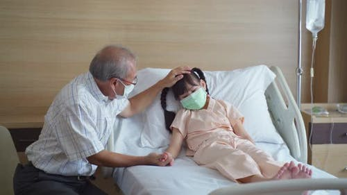 Asian young little girl kid wearing mask lying on bed in recovery room from curing the COVID 19.
