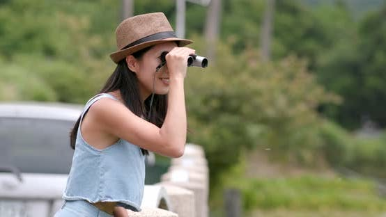 Thumbnail for Happy woman traveling and look though the binocular at outdoor landscape