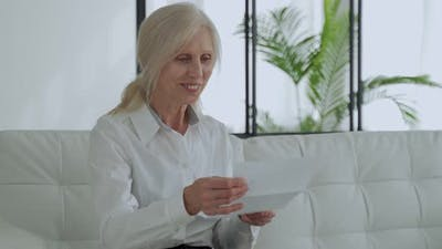 Older Woman Reading a Letter Sitting on a Sofa in the Living Room