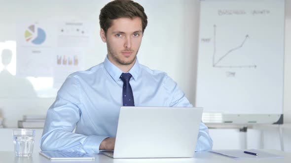 Thumbnail for Confident Young Businessman in Office Looking at Camera
