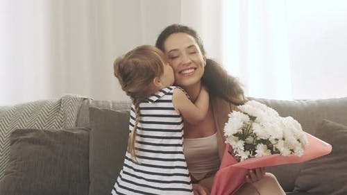 Happy Mother's Day Little Daughter Congratulates Mom and Gives Her White Flowers