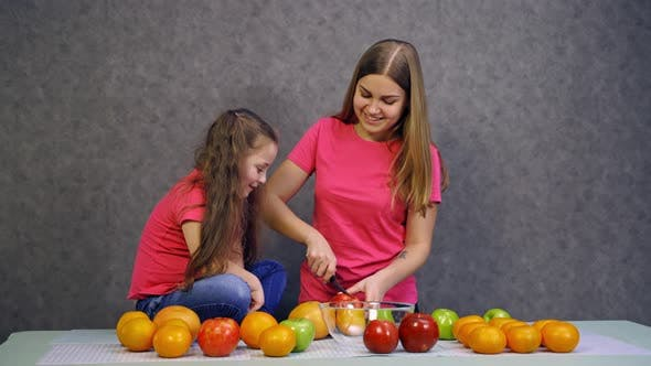 Thumbnail for Woman cutting fruits on table. Young woman with daughter preparing healthy food