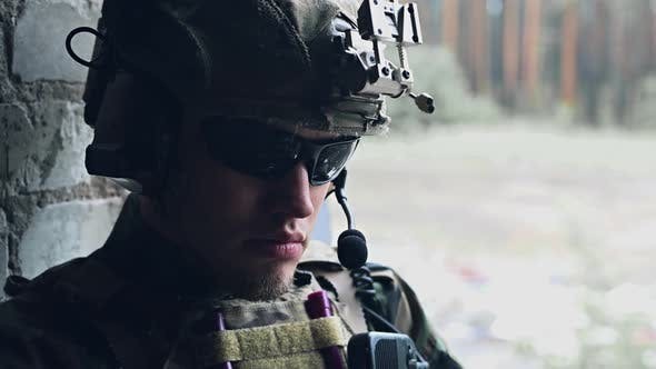 Portrait of Military Man in Glasses, Army Helmet and Walkie-talkie Sitting and Looking Around. Face