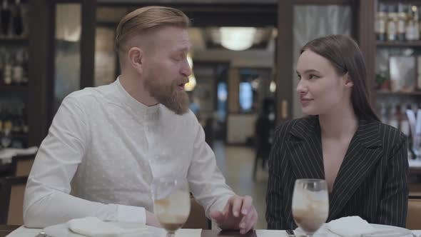 Thumbnail for Mature Man Telling Story To a Beautiful Young Woman in the Restaurant Table