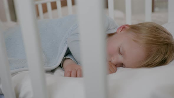 Thumbnail for Lovely Cheerful Carefree Male Kid Sleeps and Sees Happy Dreams in His Comfortable Sack in a Crib