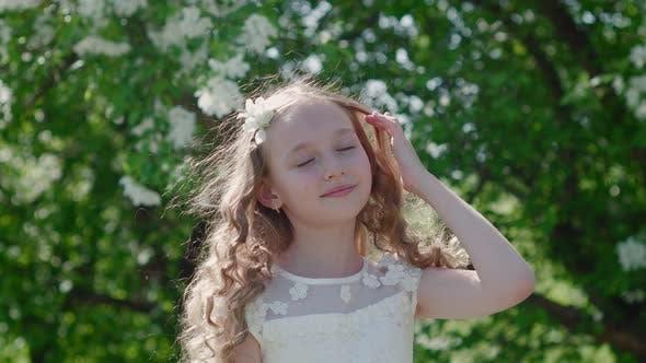 Cover Image for Porträt Romantisches Mädchen mit lockigem Haar Wicklung im Wind in blühenden Garten. Schönes junges Mädchen in
